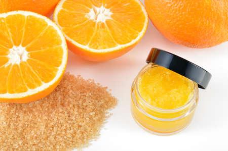 Natürliches Orangenzucker Lippenpeeling auf weißem Hintergrund mit Reflexion orange Kosmetik in einem Glas mit Orangen in einem Hintergrund