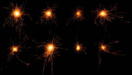 Set of burning sparklers isolated on black background  Small fireworks giving off sparks of fire  Sparks explosion  photo