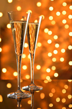 Two glasses of champagne on a reflective table against bokeh background. photo