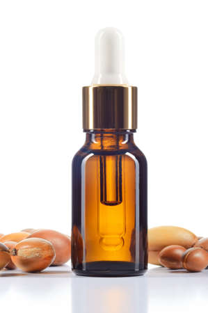 Argan oil and argan nuts isolated on white background  Body oil in brown bottle