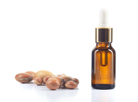Argan oil and group of argan nuts isolated on white background  Body oil in brown bottle