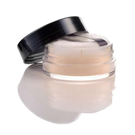 白い背景で隔離のパフが付いている瓶に半透明のルース パウダー 写真素材