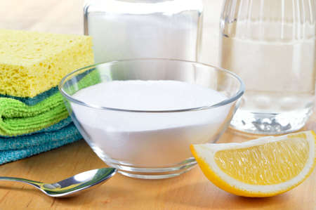 Eco-friendly natural cleaners  Vinegar, baking soda, salt, lemon and cloth on wooden table  Homemade green cleaning  photo