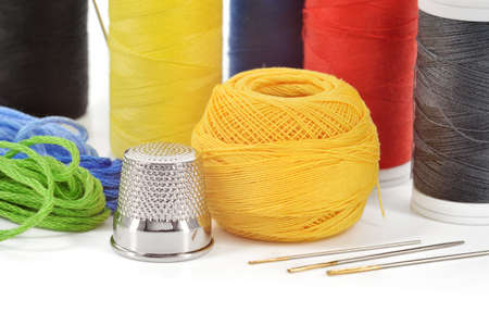 haberdashery: Sewing accessories  Few needles, threads and thimble isolated on white background