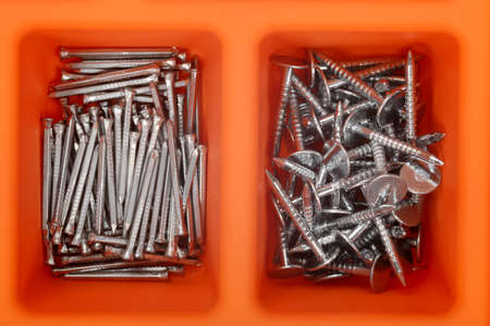 Close up of different types of nails in an orange plastic box  Order in toolbox  photo