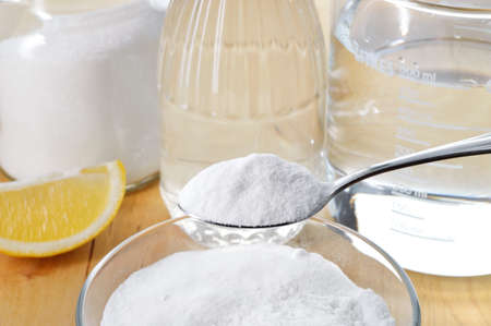 Eco-friendly natural cleaners  Vinegar, baking soda, salt, lemon and cloth on wooden table  Homemade green cleaning  Stock Photo