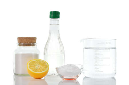 cleaning products: Respetuoso del medio ambiente limpiadores naturales vinagre, bicarbonato de sodio, la sal, el limón y el agua en una taza de medir en el fondo blanco hecho en casa de limpieza verde