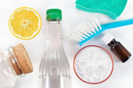 Respetuoso del medio ambiente limpiadores naturales vinagre, bicarbonato de sodio, la sal, el limón y el aceite esencial de limpieza casera verde sobre fondo blanco