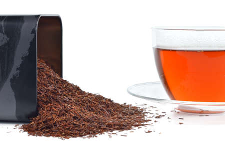 Natural organic rooibos in a tin and cup of rooibos tea  Tisane tea without caffeine isolated on white background  photo
