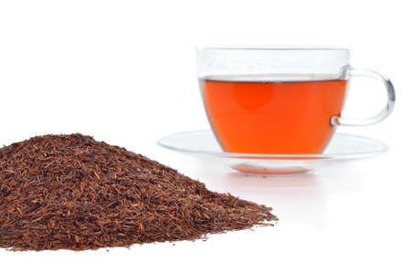 Natural organic rooibos in a cup and pile of rooibos tea  Tisane tea without caffeine isolated on white background