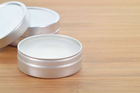 Pure shea butter in metallic tin on wooden background  Perfect lip balm and beauty balm  Plenty of copy space  photo