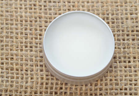 Pure shea butter in metallic tin on linen canvas background  Perfect lip balm and beauty balm