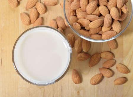 Mandelmilch als Ersatz für Kuhmilch Glas Mandelmilch und Mandeln auf einem Holztisch Standard-Bild - 28449295