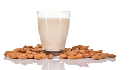 アーモンド ミルクとアーモンドの白い背景で隔離のヒープの酪農の牛乳ガラスの代用としてアーモンド ミルク