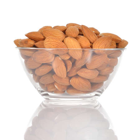 studio b: Almonds in a glass bowl isolated on white background  Healthy snack