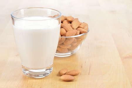 Mandelmilch als Ersatz für Kuhmilch Glas Mandelmilch und Schüssel Mandeln auf einem Holztisch Standard-Bild - 28920509