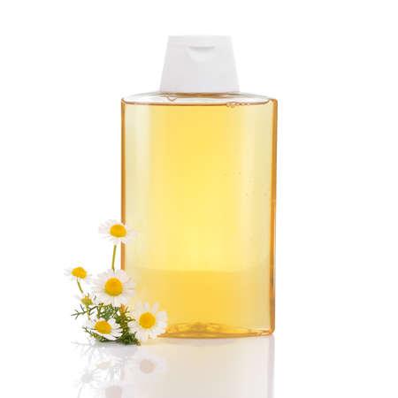 jabon liquido: Champú para el pelo suavemente con manzanilla y flores de manzanilla aislados en el fondo blanco destacado e ilumina el cabello rubio