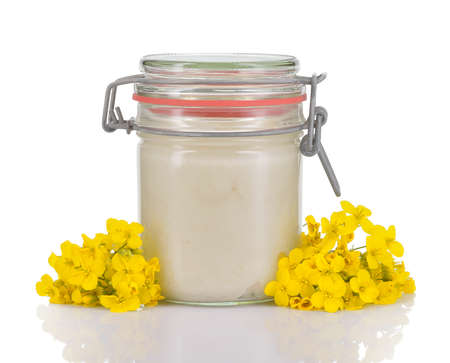 oilseed rape: Crystallized rapeseed or canola honey in a glass jar with rapeseed flowers isolated on white background  White honey with a creamy smooth texture  Stock Photo
