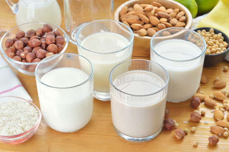 soya: Different vegan milks on a table  Hazelnut, rice, soya and almond milk  Substitute for dairy milk