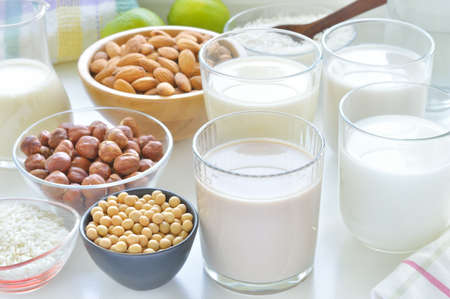 Different vegan milks on a table  Hazelnut, rice, soya and almond milk  Substitute for dairy milk