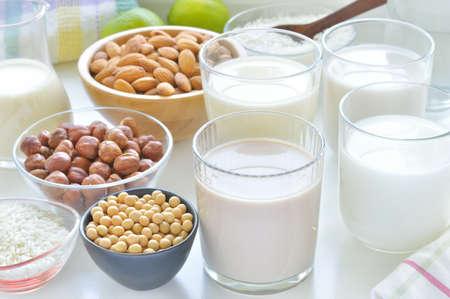 mleko: Różne wegańskie mleko na stole z orzechów laskowych, ryżu, soi i mleka migdałowego zastępujących mleko mleczarskiego