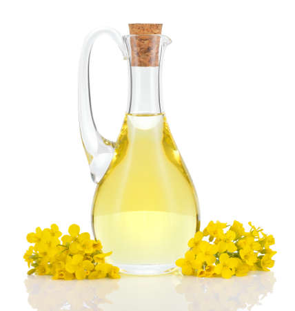 Rapeseed oil in decanter and oilseed rape flowers isolated on white background  Canola oil