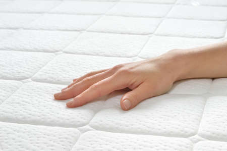 beds: Choosing mattress and bed. Close-up of female hand touching and testing mattress in a store. Copy space.