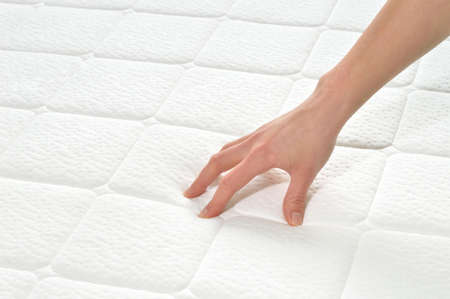 mattress: Choosing mattress and bed. Close-up of female hand touching and testing mattress in a store. Copy space.