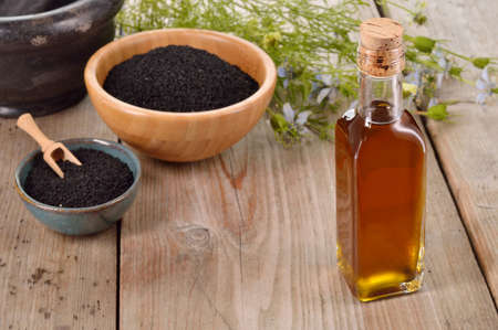 Nigella sativa oil in a bottle and nigella seeds and flowers on wooden background. Black cumin healing herb. Cold pressed, non refined oil. Traditional medicine.