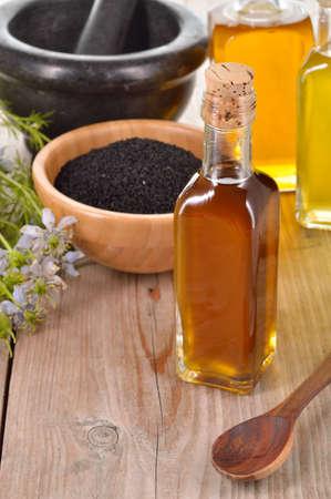 Nigella sativa Öl in einer Flasche und Nigellasamen und Blumen auf Holzuntergrund. Schwarzkümmel Heilkraut. Kaltgepresstes, nicht raffiniertes Öl. Traditionelle Medizin.