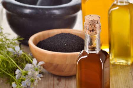 Close-up der Nigella sativa Öl in einer Flasche, gegen die von Nigellasamen und Blumen auf Holzuntergrund. Schwarzkümmel Heilkraut. Kaltgepresstes, nicht raffiniertes Öl. Traditionelle Medizin.