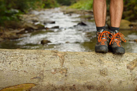 river trunk: Hiking shoes legs on tree trunk, mountain trail. Stock Photo