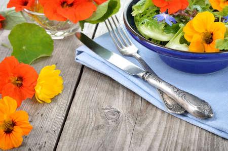 Frischer Sommersalat mit essbaren Blüten Kapuzinerkresse, Borretschblüten in eine Schüssel geben. Copyspace.