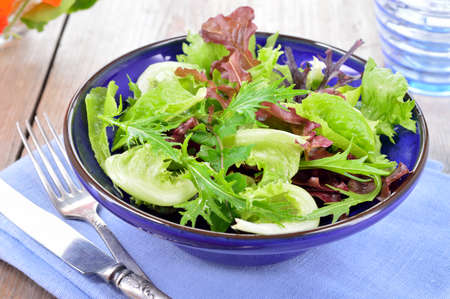 Fresh light mixed green leaves salad. Lettuce, mizuna, arugula and oakleave lettuce in blue bowl on a table. photo