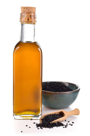Nigella sativa oil in a bottle and nigella or black cumin seeds in a bowl isolated on white background. Unsaturated fats Omega-6 fatty acids. Cold pressed, non refined oil. Anti-aging ingredient.