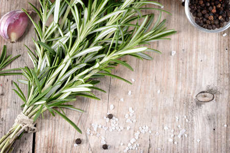 Fresh bunch of rosemary, garlic, pepper and salt on wooden table. Aromatic evergreen herb, many culinary - roasted meats. Copyspace. photo