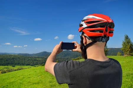 Radfahrer Fotografieren mit Smartphone. Kaukasischen Mann im Fahrradhelm unter Smartphone-Foto von Bergen. Aktivität im Freien. Standard-Bild - 34028311