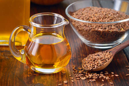 linseed: Brown flax seeds on spoon and flaxseed oil in glass jug on wooden table. Flax oil is rich in omega-3 fatty acid.