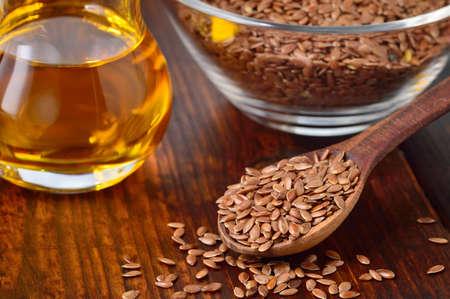 Semillas de lino de Brown en la cuchara y el aceite de linaza en jarra de cristal en la mesa de madera. El aceite de linaza es rica en ácidos grasos omega-3.