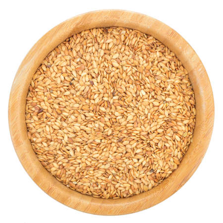 linum usitatissimum: Golden flax seeds in wooden bowl isolated on white background. Flax seeds are rich in omega-3 fatty acid. Top view.