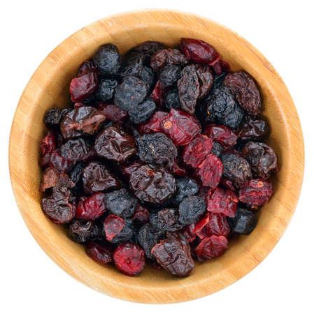 ミックス ベリー フルーツを乾燥させます。乾燥クランベリー、レーズン、サワー チェリー、白い背景で隔離の木製ボウルにブルーベリー。平面図