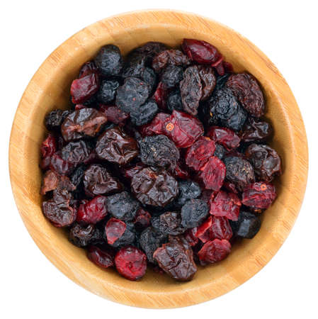 Dried mix berries fruits. Dried cranberries, raisins, sour cherries, blueberries in wooden bowl isolated on white background. Top view.