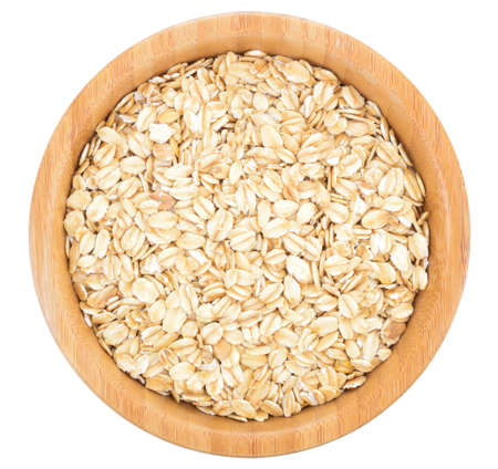 rolled oats: Rolled oats in wooden bowl isolated on white background.