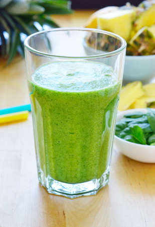 pineapple  glass: Green spinach and pineapple smoothie on table. Fruit smoothie made with baby spinach leaves, pineapple, banana and pear