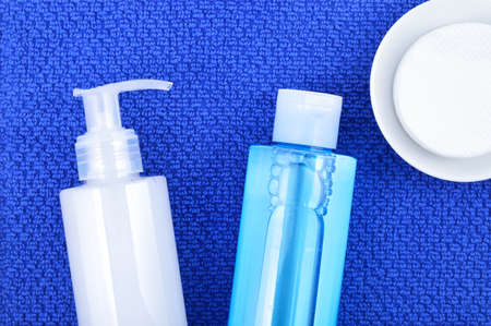 Daily cleansing cosmetics - face wash cleansing gel, smoothing toner and cotton cleansing pads on navy blue towel.