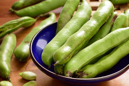 fava: Broad beans fava beans in a bowl on wooden table. Summer vegetables, legumes. Angle view. Stock Photo