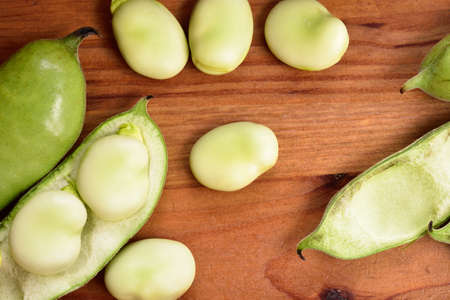 fava: Broad beans fava beans on wooden table. Summer vegetables, legumes. Top view. Stock Photo