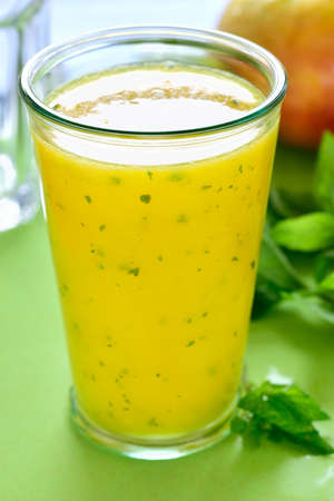 lime juice: Cooling mint mango smoothie, summer drink on green table, Yellow Tropical Smoothie made with mango, mint and lime juice.