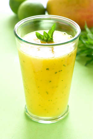 green mango: Cooling mint mango smoothie, summer drink on green table, Yellow Tropical Smoothie made with mango, mint and lime juice.