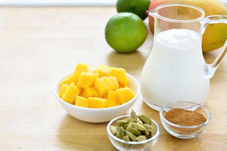 cardamon: Mango lassi ingredients. Mango and yogurt, yoghurt, cardamon, cinnamon. Selective focus. Copy space.